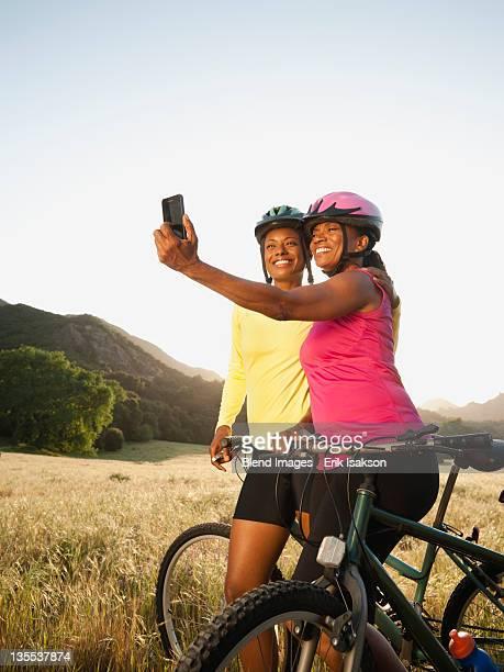Friends taking self-portrait next to mountain bikes