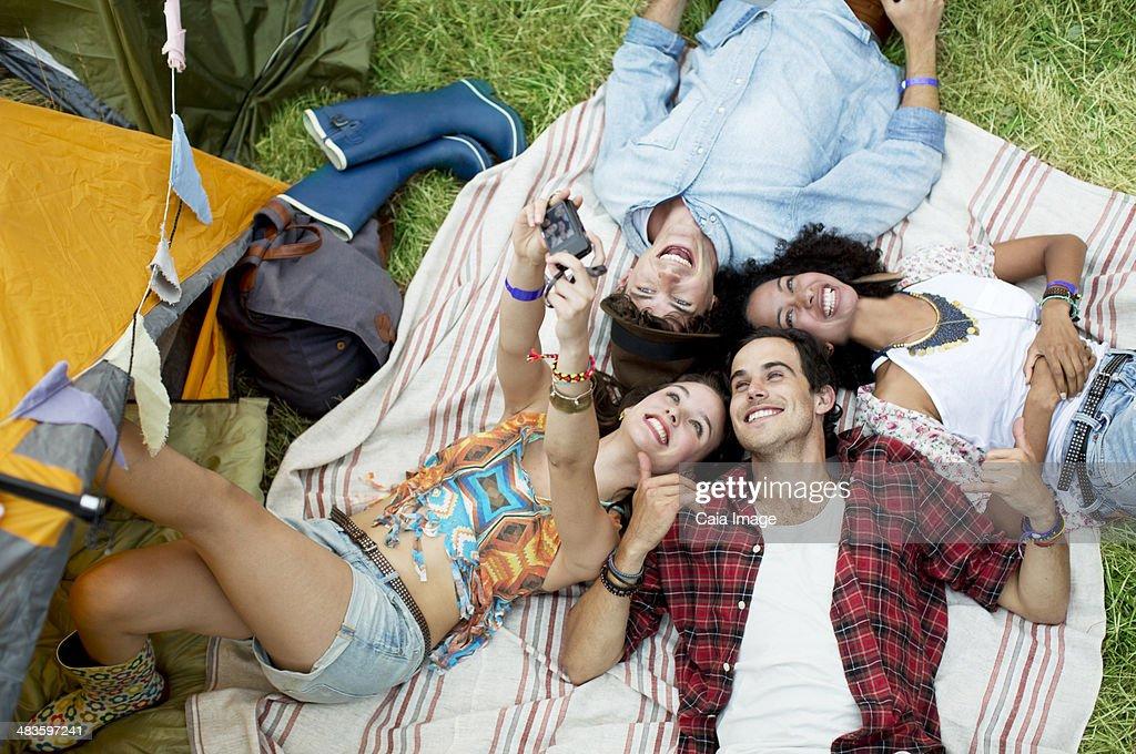 Friends taking self-portrait on blanket outside tent at music festival : Stock Photo