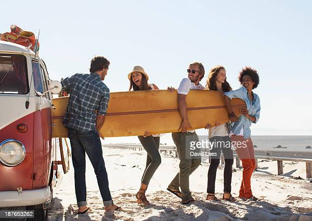 Friends taking surfboard out of camper van