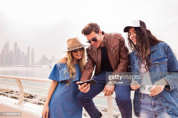 friends talking about social media using a smartphone - social media marketing stock pictures, royalty-free photos & images