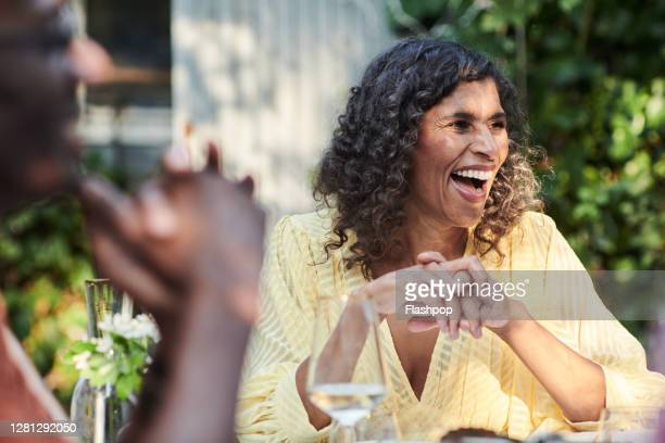 friends talking and dining outside on a warm summers day. - mature adult stock pictures, royalty-free photos & images