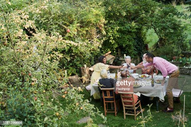 friends talking and dining outside on a warm summers day. - {{relatedsearchurl(carousel.phrase)}} stock pictures, royalty-free photos & images