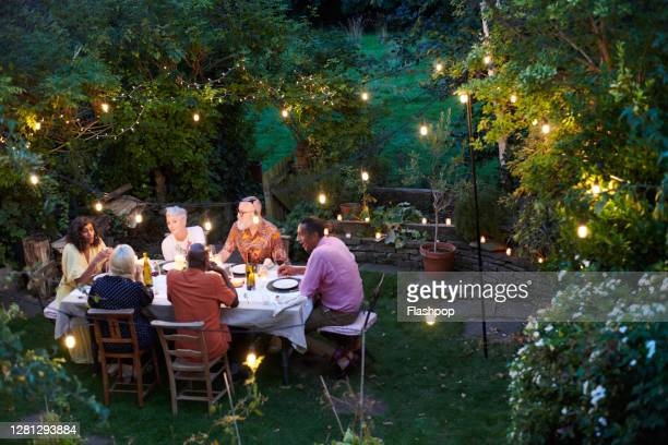 friends talking and dining outside on a warm summers evening. - {{relatedsearchurl(carousel.phrase)}} stock pictures, royalty-free photos & images