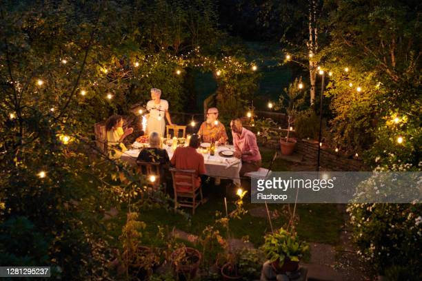 friends talking and dining outside on a warm summers evening. - refreshment stock pictures, royalty-free photos & images