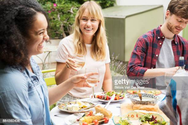 Friends talking and laughing at dinnerparty in garden.