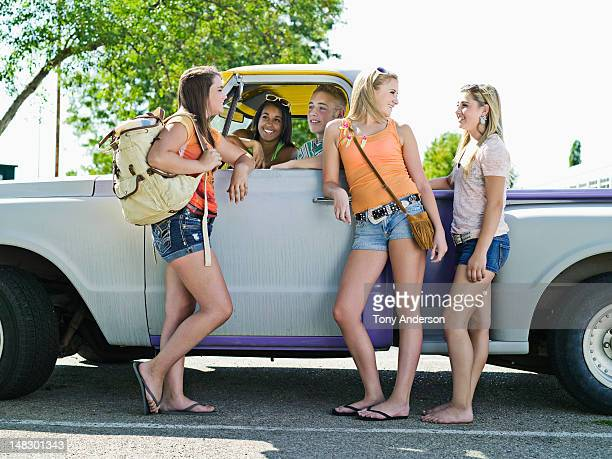 Friends talking around pickup truck