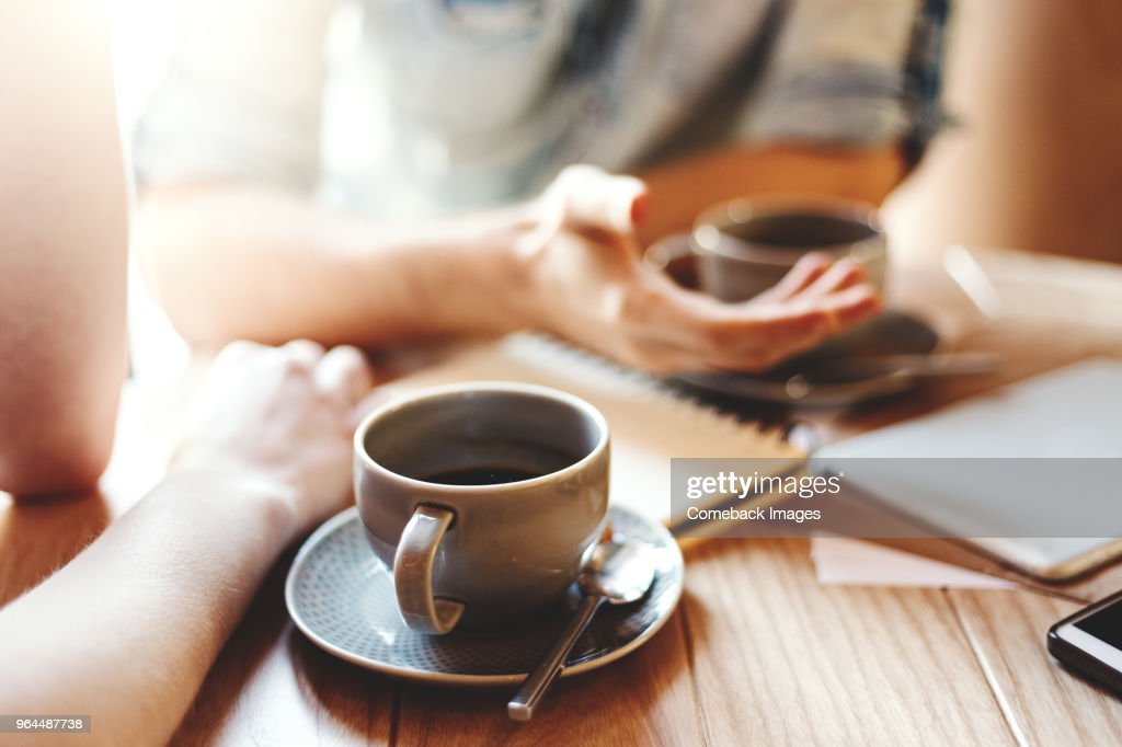 Friends talking at cafe table during coffee break. Unrecognizable male and female colleagues discussing business issues, focus on coffee cup with saucer and teaspoon : Stock Photo