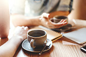 Friends talking at cafe table during coffee break. Unrecognizable male and female colleagues discussing business issues, focus on coffee cup with saucer and teaspoon
