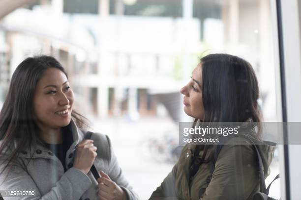 friends talking in front of shop window - sigrid gombert stock pictures, royalty-free photos & images