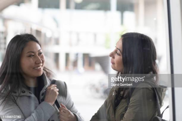 friends talking in front of shop window - sigrid gombert - fotografias e filmes do acervo