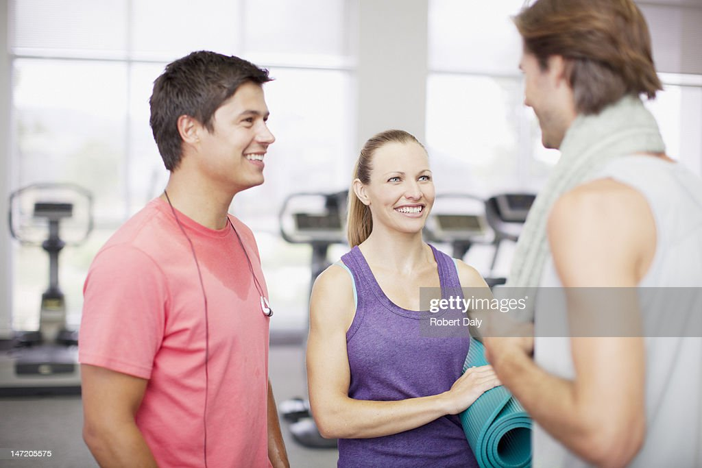 Friends talking in gymnasium : Stock Photo