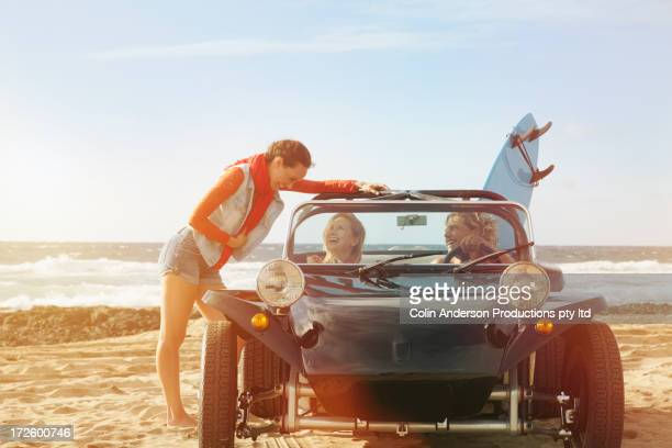 Friends talking in jeep on beach
