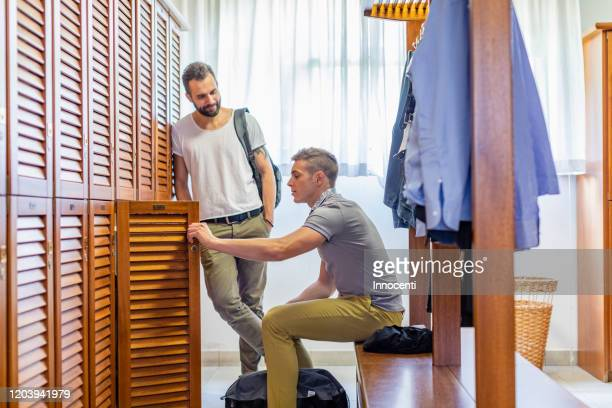 friends talking in locker room - locker room stock pictures, royalty-free photos & images