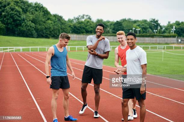 friends talking on running track - outdoors stock pictures, royalty-free photos & images