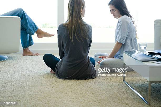 Friends talking together in living room