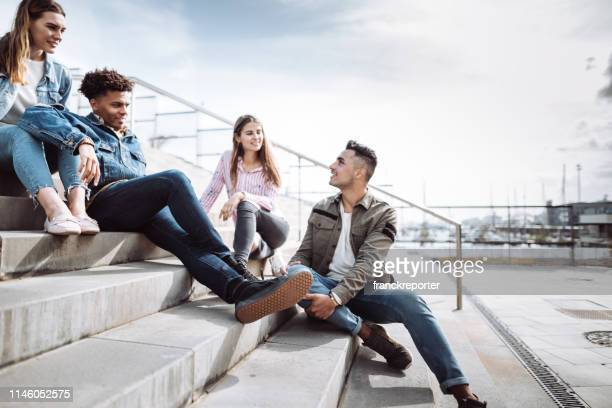 friends talking together in the steps - bench stock pictures, royalty-free photos & images