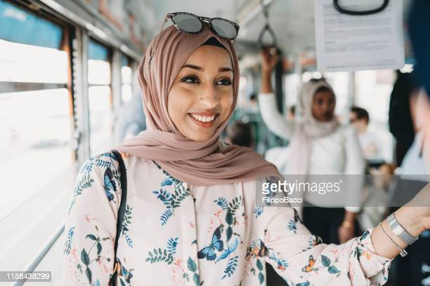 friends talking together inside a bus in the city - north african ethnicity stock pictures, royalty-free photos & images