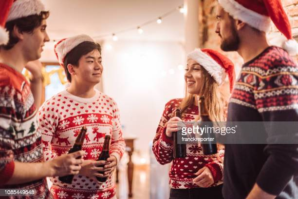 friends talking togetherness at the christmas party - ugly christmas sweater stock photos and pictures