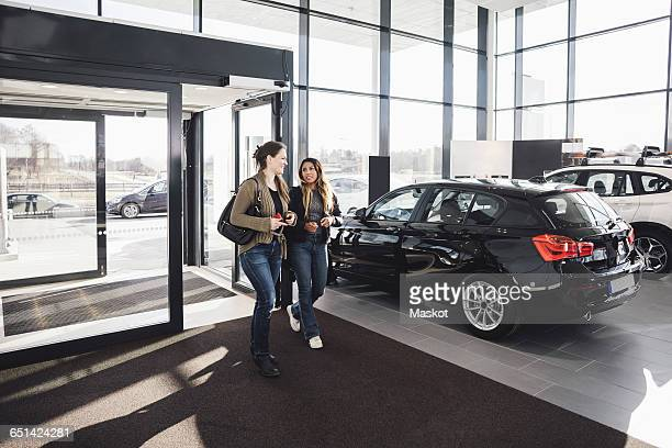 Friends talking while entering in car showroom