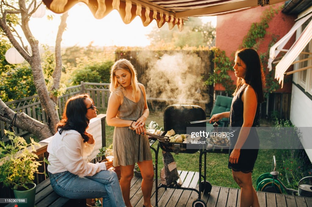 Friends talking while grilling food on barbecue for dinner party in yard : Stock Photo