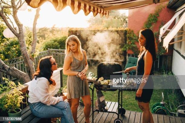 friends talking while grilling food on barbecue for dinner party in yard - amigas fotografías e imágenes de stock