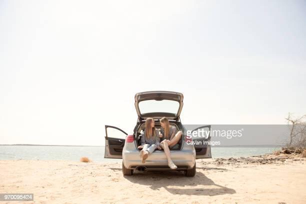 friends talking while sitting in car trunk against clear sky - bota fotografías e imágenes de stock