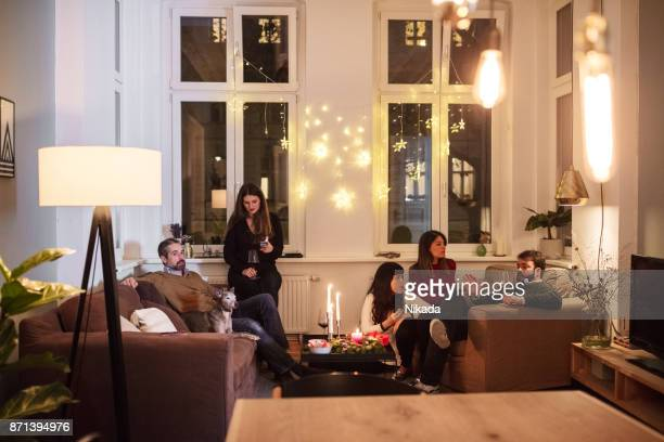 friends talking while sitting in living room during christmas party - home after party stock pictures, royalty-free photos & images