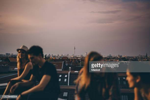friends talking while sitting on terrace during rooftop party in city at dusk - dach stock-fotos und bilder