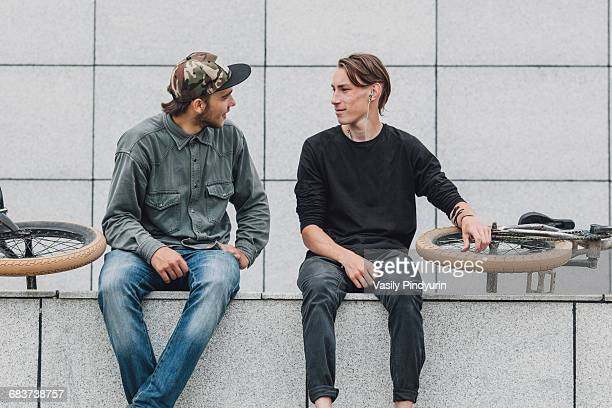 Friends talking while sitting with bicycles against wall at skateboard park