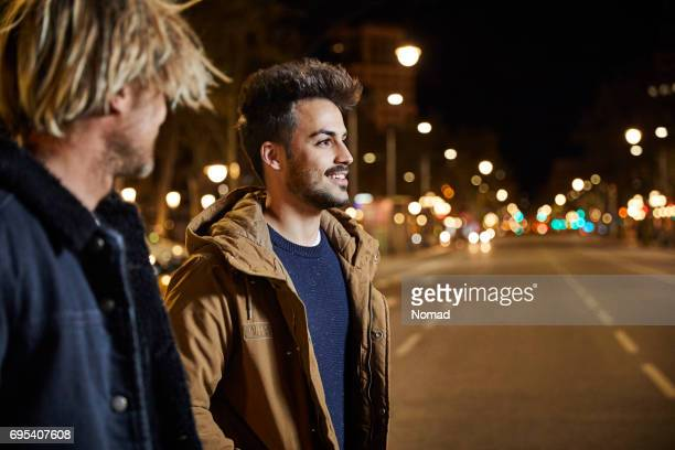 friends talking while walking in city at night - only young men stock pictures, royalty-free photos & images