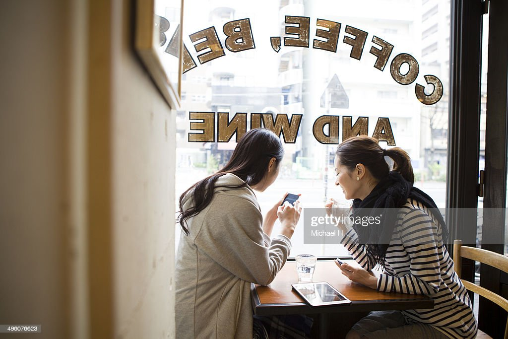 friends talking with smartphones at  cafe : Stock Photo