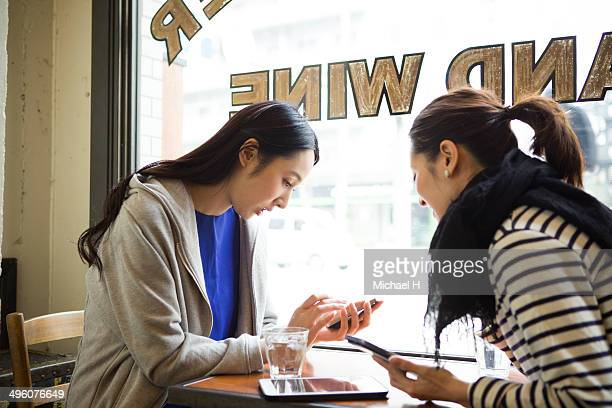 friends talking with smartphones at  cafe