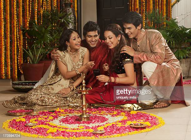Friends text messaging on a mobile phone on Diwali