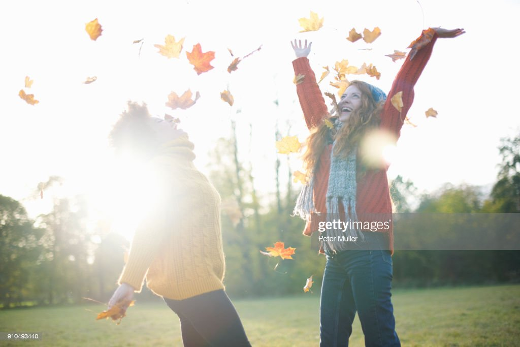 Friends throwing autumn leaves in air : Stock Photo