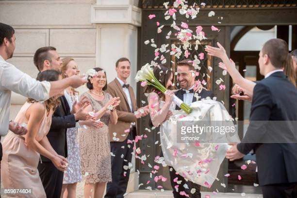 Friends throwing petals on wedding couple