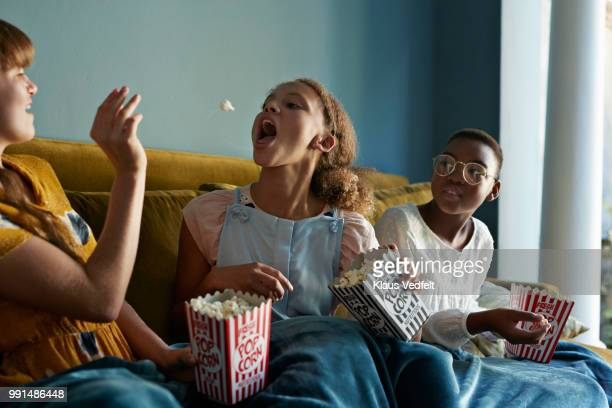 friends throwing popcorn and catching with mouth, at home - lanciare foto e immagini stock