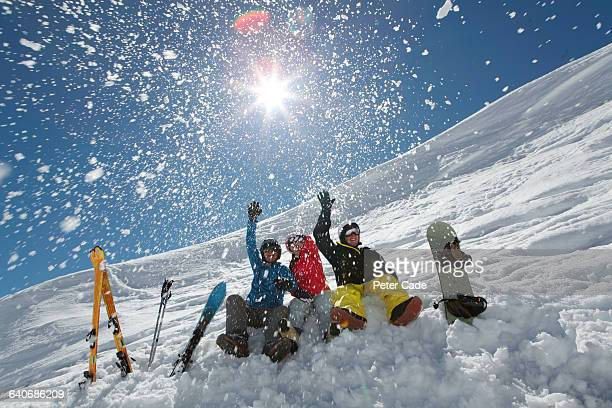 Friends throwing snow sat on ski slope