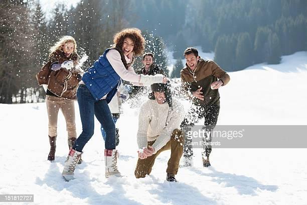 Amigos tirando snowballs en el campo