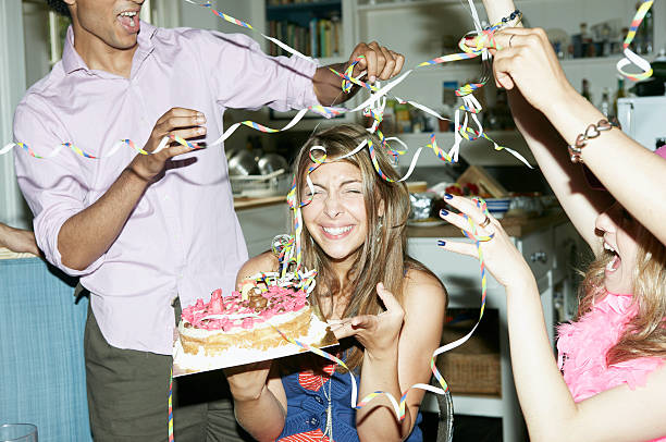 friends throwing streamers over woman holding cake - best friend birthday cake stock pictures, royalty-free photos & images
