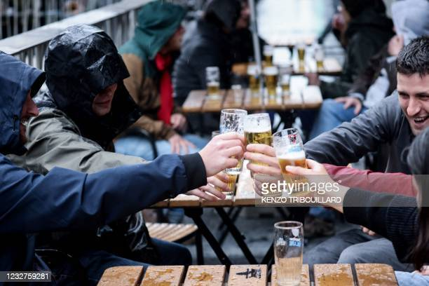 Friends toast each other as they drink a beer on a terrace in Brussels, on May 8 as the Belgium government eased the restrictions put in place to...