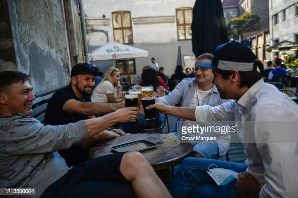 Friends toast with beer as they sit in an outside area of a pub during the first day of the third stage of easing measures due to COVID-19 on May 18,...