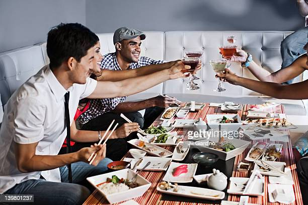 Friends toasting and eating together in restaurant