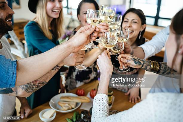 friends toasting  at a dinner party - white wine stock pictures, royalty-free photos & images
