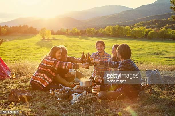 friends toasting beer bottles on field - food and drink stockfoto's en -beelden