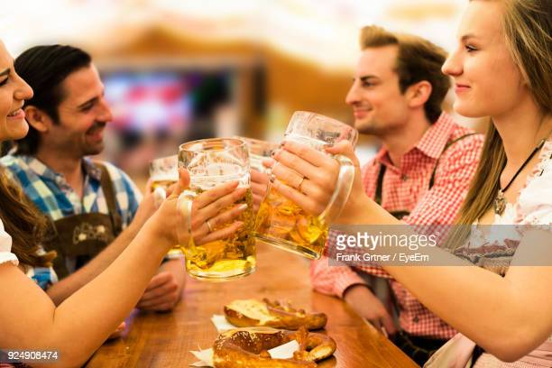 friends toasting beer glasses at restaurant - oktoberfest stock pictures, royalty-free photos & images