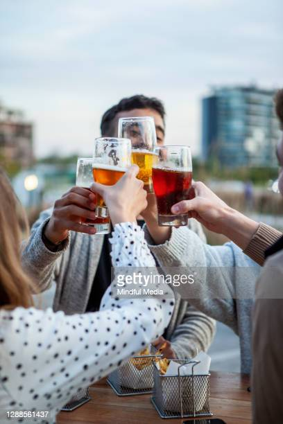 friends toasting beer glasses during sunset - honour stock pictures, royalty-free photos & images