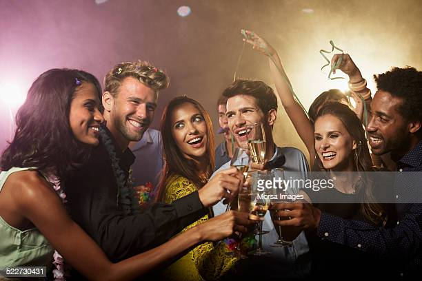 Friends toasting champagne flutes at nightclub