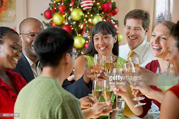 Friends toasting champagne glasses at Christmas dinner