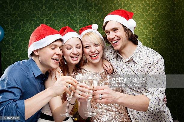 Friends toasting champagne,wearing Christmass hats
