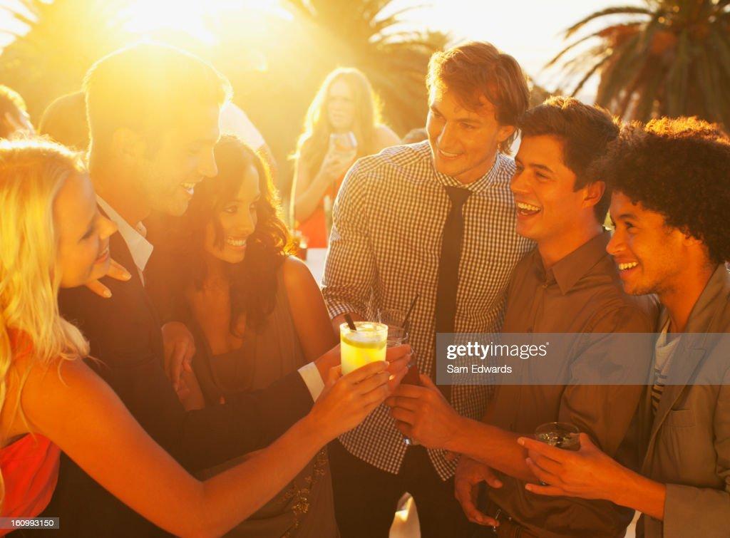 Friends toasting cocktails on sunny balcony : Bildbanksbilder